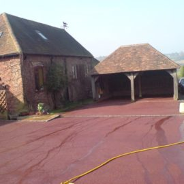 Red tarmacadam driveway installation